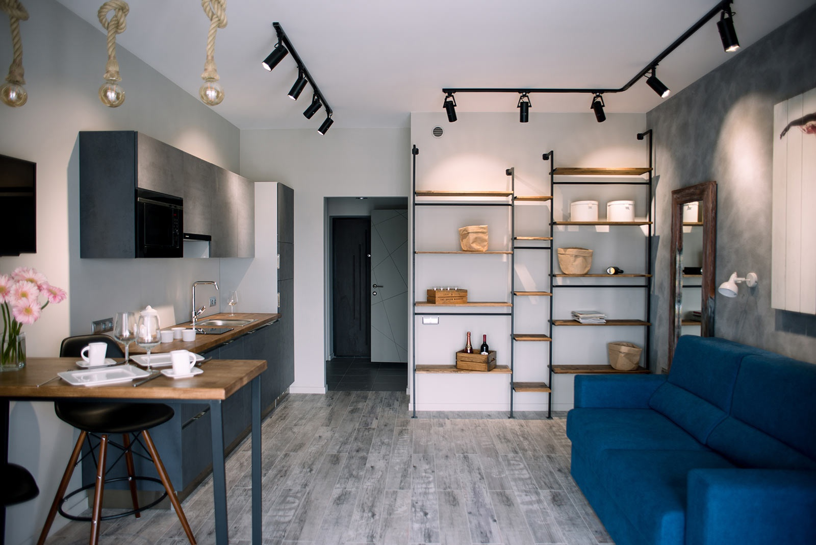 Трековые светильники в кухне с гостинной в качестве акцентной подсветки фасада кухни и стелажей с предметами интерьера.